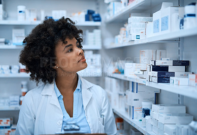 Buy stock photo Shot of a young woman doing inventory in a pharmacy