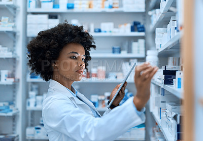 Buy stock photo Shot of a young woman using a digital tablet to do inventory in a pharmacy
