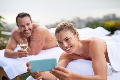 Buy stock photo Shot of a couple taking selfies while enjoying themselves at a day spa