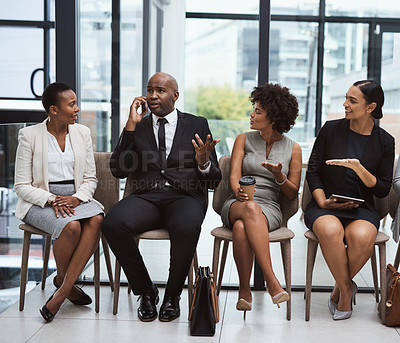 Buy stock photo Shot of a group of businesspeople looking annoyed at a businessman talking on a cellphone while waiting in line in an office