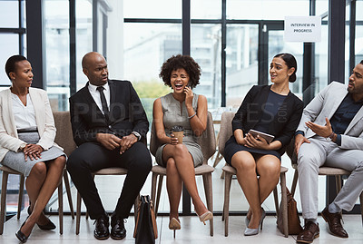 Buy stock photo Shot of a group of businesspeople looking annoyed at a businesswoman talking on a cellphone while waiting in line in an office
