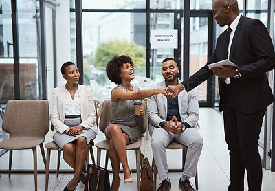 Buy stock photo Shot of two businesspeople shaking hands during an interview in an office