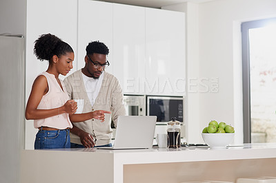 Buy stock photo Shot of a young couple using a laptop at home