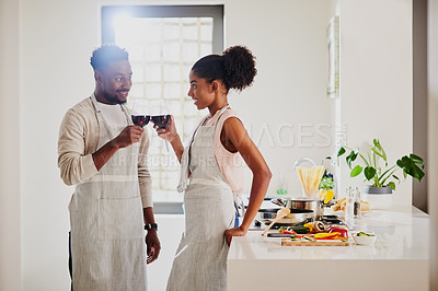 Buy stock photo Cropped shot of a young couple enjoying some wine while cooking