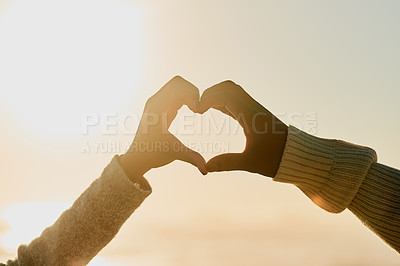 Buy stock photo Cropped shot of a couple forming a heart shape with their hands at the beach