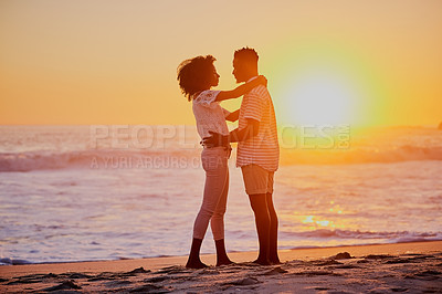 Buy stock photo Shot of a young couple on the beach at sunset