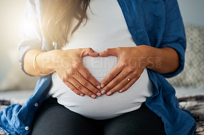 Buy stock photo Closeup shot of an unrecognizable pregnant woman making a heart shape with her hands on her belly at home