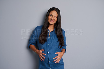 Buy stock photo Studio portrait of a pregnant woman posing against a grey background