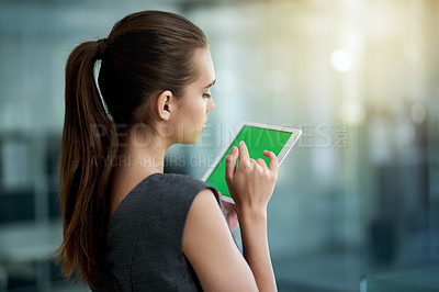 Buy stock photo Shot of a young businesswoman using a digital tablet with a green screen in an office