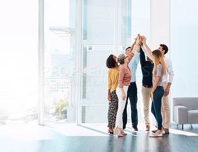 Buy stock photo Full length shot of a group of creative colleagues high fiving in celebration in their modern office