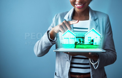 Buy stock photo Studio shot of a young businesswoman using a digital tablet with property graphics against a blue background