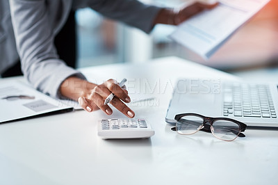 Buy stock photo Cropped shot of a businesswoman using a calculator at her desk in a modern office