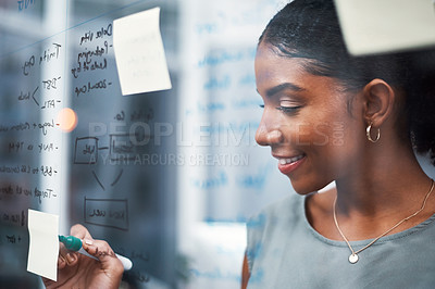 Buy stock photo Shot of a young businesswoman brainstorming with sticky notes on a glass screen in modern office