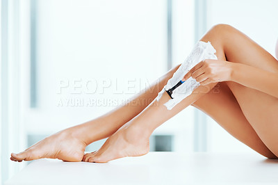 Buy stock photo Cropped shot of an unrecognizable woman shaving her legs in the bathroom at home