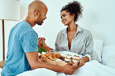 Buy stock photo Cropped shot of an affectionate young couple having breakfast in bed