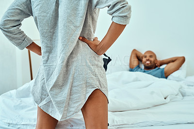 Buy stock photo Rearview shot of a woman teasing her husband in the bedroom