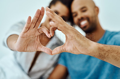 Buy stock photo Defocused shot of a couple forming a heart with their hands