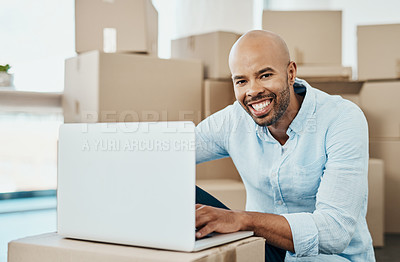 Buy stock photo Portrait of a young man using a laptop while moving house