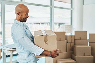Buy stock photo Shot of a young man carrying a box while moving house
