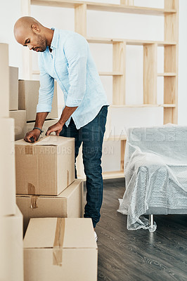 Buy stock photo Shot of a young man unpacking boxes while moving house