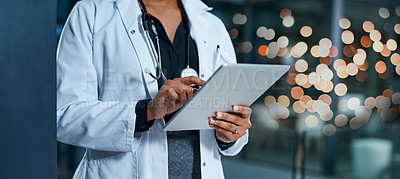 Buy stock photo Closeup shot of an unrecognizable doctor using a digital tablet in a hospital at night