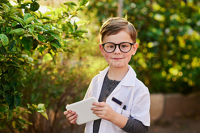 Buy stock photo Portrait of an adorable little boy pretending to be a scientist by exploring the plants outside using a tablet