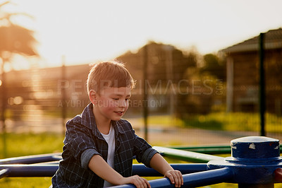 Buy stock photo Cropped shot of an adorable little boy playing with the merry go round at a playground outside