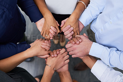 Buy stock photo High angle shot of a group of businesspeople holding their hands together in solidarity