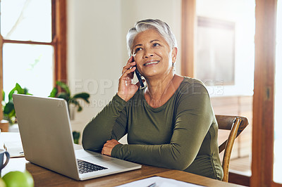 Buy stock photo Shot of a mature woman talking on a cellphone while working on a laptop at home