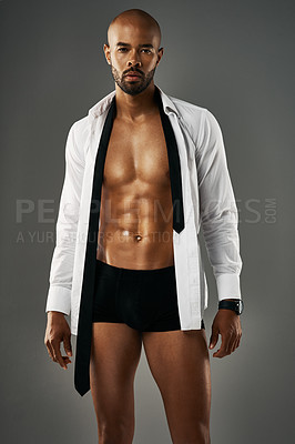 Buy stock photo Studio portrait of a sexy young man showing off his abs against a gray background