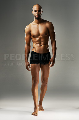 Buy stock photo Studio portrait of a sexy young man against a gray background in his underwear