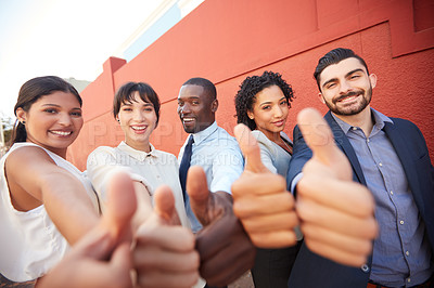 Buy stock photo Shot of a group of businesspeople showing thumbs up outdoors
