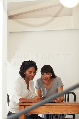 Buy stock photo Shot of two young businesswomen using a mobile phone together in a modern office