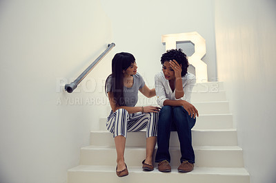 Buy stock photo Shot of a young businesswoman comforting her colleague on the steps in a modern office