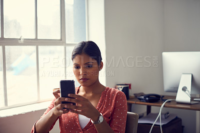 Buy stock photo Shot of a young businesswoman using a mobile phone at her desk in a modern office