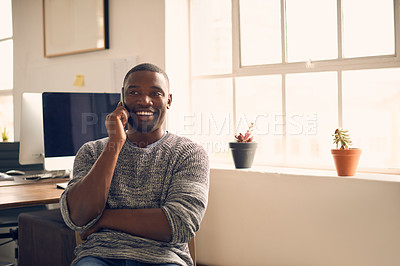 Buy stock photo Shot of a young businessman using a mobile phone at his desk in a modern office