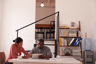 Buy stock photo Shot of a young businessman and businesswoman using a digital tablet while discussing paperwork in a modern office