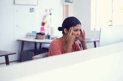 Buy stock photo Shot of a young businesswoman looking stressed while using a computer in a modern office