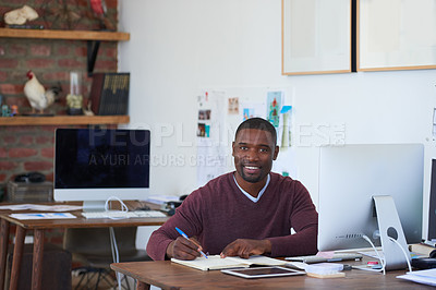 Buy stock photo Portrait of a young businessman writing notes at his desk in a modern office