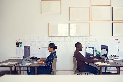 Buy stock photo Shot of a young businessman and businesswoman using their computers in a modern office