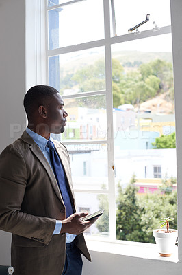 Buy stock photo Shot of a young businessman using a cellphone while looking out a window in an office
