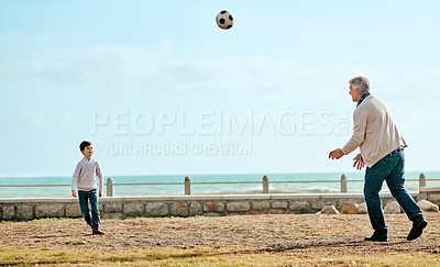 Buy stock photo Full length shot of an adorable little boy and his grandfather kicking a soccer ball outside