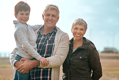 Buy stock photo Cropped shot of an adorable little boy and his grandparents standing outside at the beach