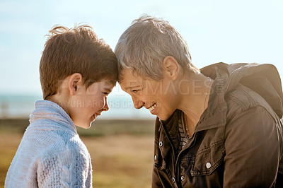 Buy stock photo Cropped shot of an adorable little boy and his grandmother face to face outside