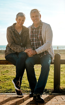 Buy stock photo Full length portrait of an affectionate senior couple sitting on a wooden railing at the beach