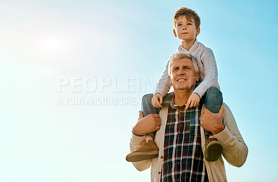 Buy stock photo Cropped shot of an adorable little boy sitting on his grandfather's shoulders outside