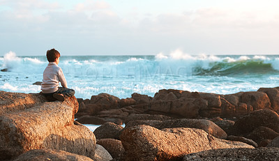 Buy stock photo Rearview shot of an adorable little boy sitting on the beach