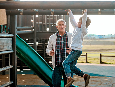 Buy stock photo Full length shot of an adorable little boy playing on an outdoor jungle gym with his grandfather