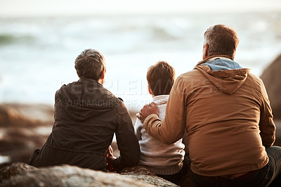 Buy stock photo Rearview shot of an adorable little boy and his grandparents sitting on the beach
