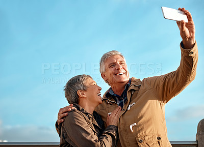 Buy stock photo Cropped shot of an affectionate senior couple taking selfies at the beach